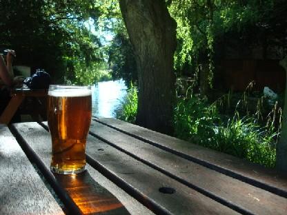 小川のほとりのテーブルでビールを飲む.JPG